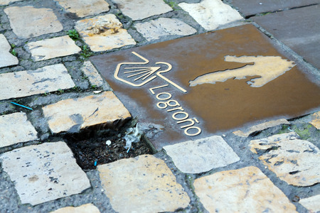 way of st  james: LOGRONO, SPAIN - JUNE 28, 2014: Sign of way of St. James (Camino de Santiago), laid on the pavement. Modern symbol of the way