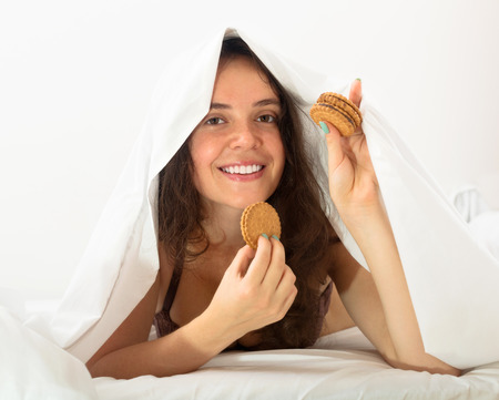 furtively: Smiling young woman eating sweet cookies on white sheet in bed