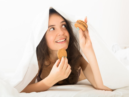 young  girl eating sweet chocolate chip cookies in bed at home   photo