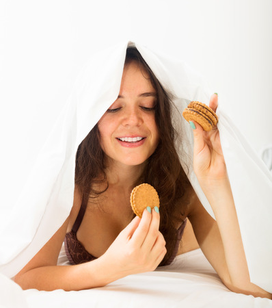 Beautiful young woman eating sweet cookies on white sheet in bed photo