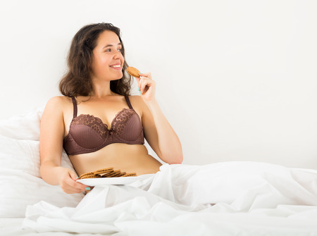 smiling girl eating sweet chocolate chip cookies in bed at home   photo