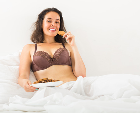 Smiling brunette girl eating chocolate chip cookies in her bed at home  photo