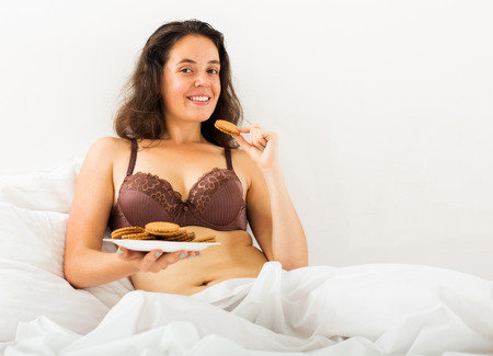 Smiling young girl eating sweet cookies in bed photo