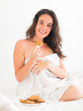 furtively: Long-haired adult girl eating chocolate chip cookies in her bed and smiling  Stock Photo