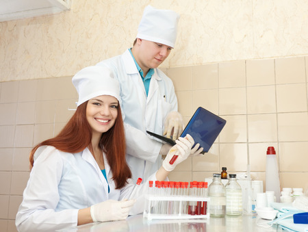 Positive nurse and male doctor works with test tubes in clinic lab  photo