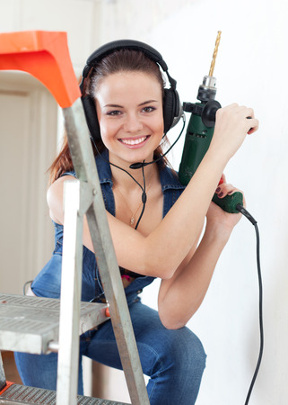 Portrait of  sexy  girl in headphones with drill on stepladder photo