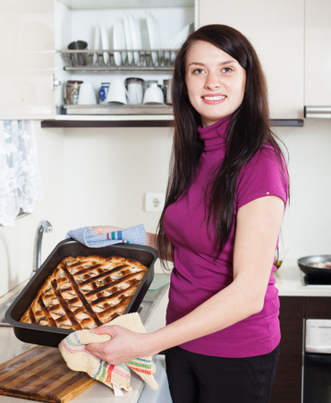 panful: Happy woman with cooked  pie in home kitchen