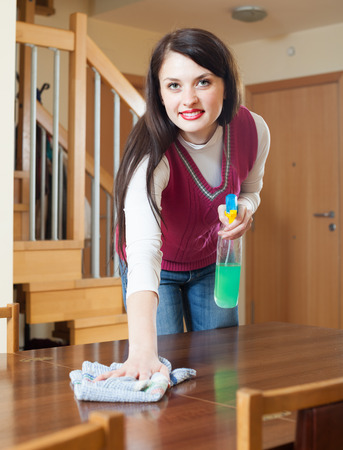 cleanser: brunette girl cleaning table with cleanser and rag in  room Stock Photo