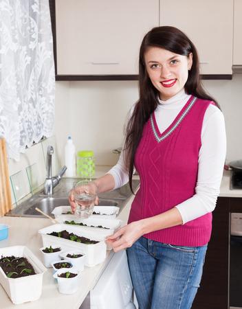 Smiling woman watering seedlings photo