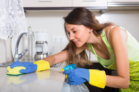 Smiling young brunette woman cleaning kitchen sink at home