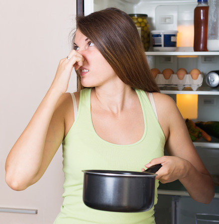 Young woman holding foul meat near refrigerator at home photo