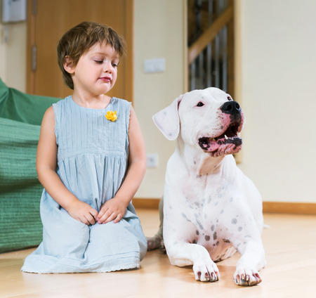 Cute little girl with big white dog lying on the floor at home. Focus on dog  photo