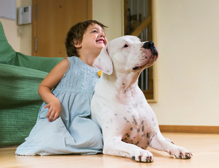 Happy smiling little girl with big white dog lying on the floor at home  photo