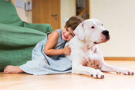 Happy cute little girl hugging white dog at home photo