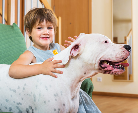 Smiling cute little girl hugging big white dog at home. Focus on dog  photo