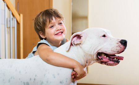Happy smiling little girl hugging friendly big white dog at home  photo