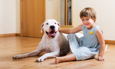 Happy smiling little girl with big white dog on the floor at home photo