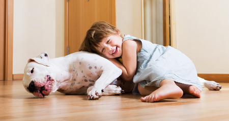 Smiling playful cute little girl hugging big white dog at home photo