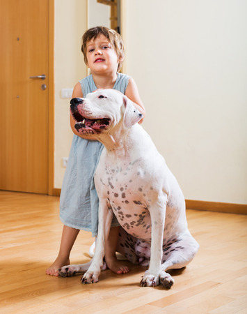 Happy cute little girl hugging friendly big white dog at home photo