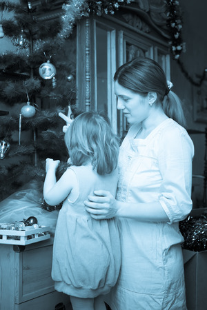 Vintage photo of young mother and daughter celebrating Christmas in home photo
