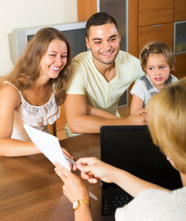 investment banking: Banking assistant and smiling young family arranging mortgage details at home. Focus on woman  Stock Photo