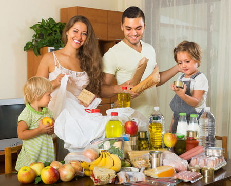 purchased: Young parents with female children sorting purchased food out indoor