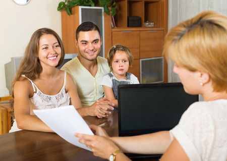 family planning: Agent helping happy family of three to obtain insurance. Focus on woman