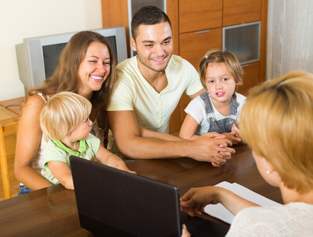 Positive young parents and two daughters sitting in front of social worker at home photo