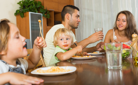 happy family of four  having lunch with pasta photo