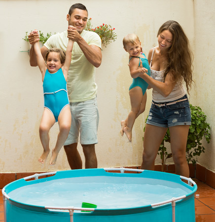 bathing suits: Cheerful little girls and parents having fun in pool at terrace. Focus on man