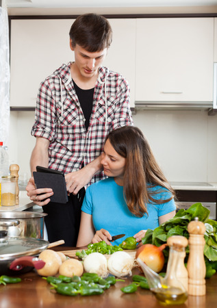 Happy man and girl cooking with electronic Book in kitchen photo