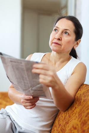 wistful:  serious and wistful mature woman with newspaper at home