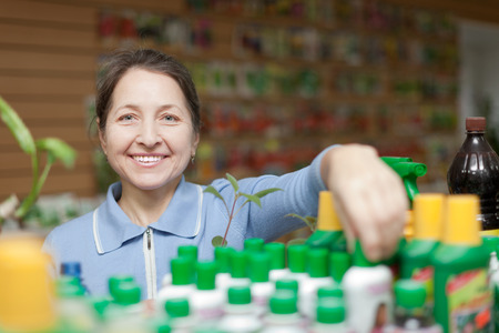 Happy female gardener chooses liquid fertilizer at garden shop photo