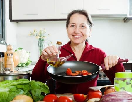 Happy  woman pouring oil into girdle at kitchen photo