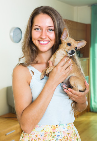 russkiy: Portrait of smiling girl holding Russkiy Toy Terrier indoor  Stock Photo