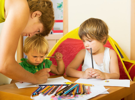 child drawing: Serious mother and children drawing with pencils at home Stock Photo