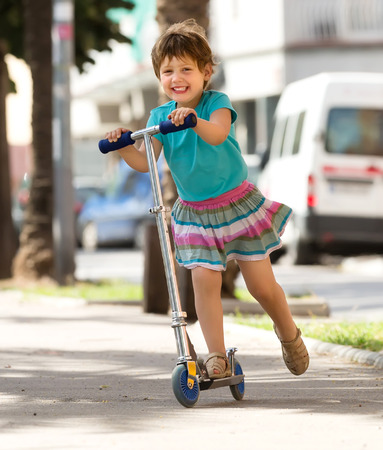 Happy little girl with scooter in park photo