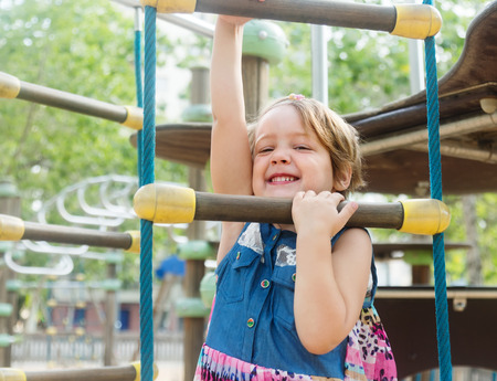 adroitness: Smiling girl developing dexterity at playground