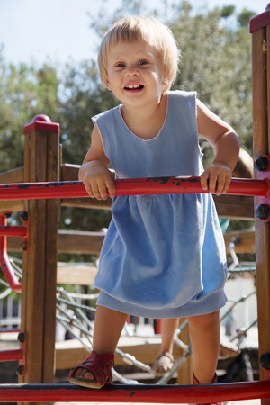 deftness: Baby girl at action-oriented playground in summer Stock Photo