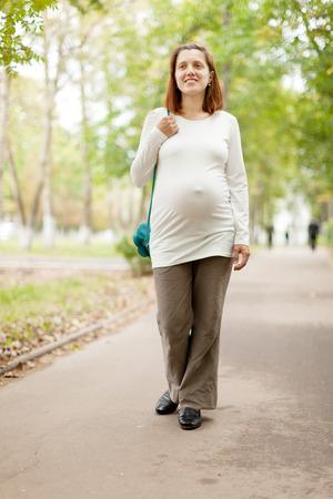 gravida: Portrait of pregnancy woman walks  summer park