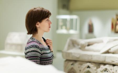 antigua grecia: Mujer joven mirando esculturas antiguas y tumbas en el museo Foto de archivo