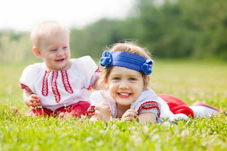 Happy children in russian folk clothes on grass meadow photo