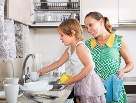 Little girl helping mother washing dishes in the kitchen. Focus on girl