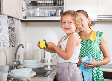 Smiling little daughter helping mother washing dishes in the kitchen. Focus on girl  photo