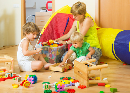 Children and mother collecting toys in plastic box Standard-Bild