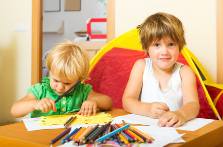 baby 4 5 years: Two little children sketching with paper and pencils in home interior