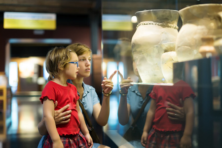 exhibition hall: mother and child looking ancient amphores in  museum