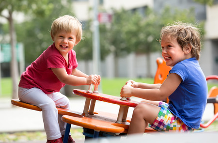 babies playing outside: Happy excited children having fun at playground in sunny day