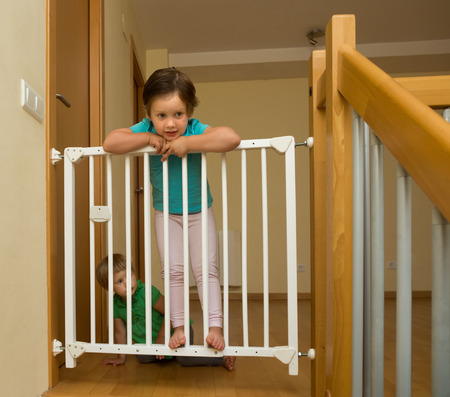 home safety: Two happy little sisters near stair gate at home
