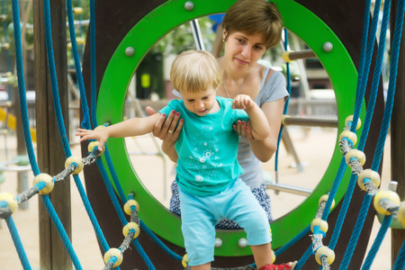 deftness: Little girl with mother at action-oriented playground in summer